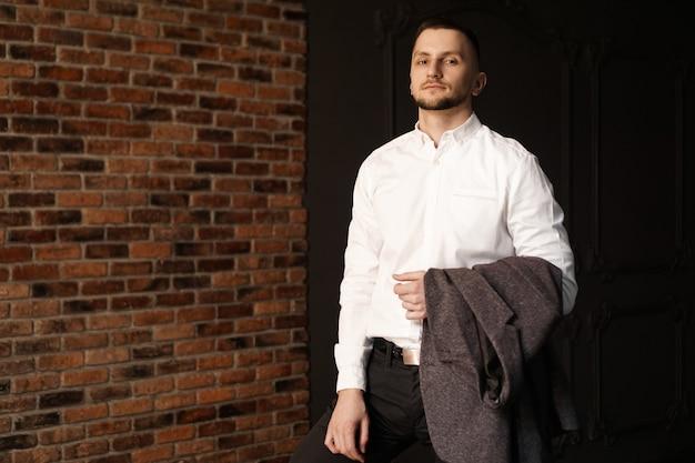 Stylowy młody biznesmen w białej koszuli trzyma kurtkę stojącą przed murem