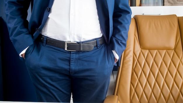 Stylowy młody biznesmen w niebieskim garniturze stojący w nowoczesnym biurze z brązowym skórzanym fotelem