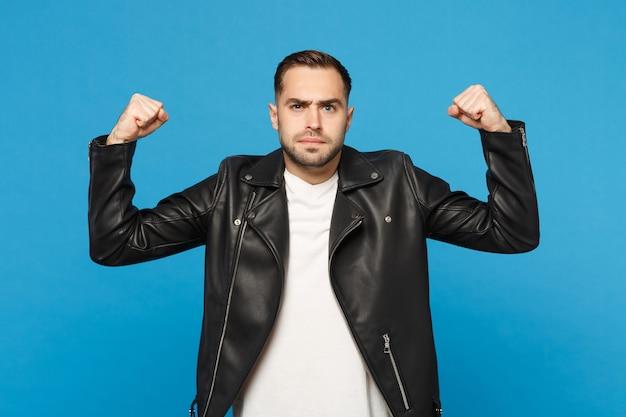Stylowy młody brodaty mężczyzna w czarnej skórzanej kurtce biały t-shirt pokazując biceps, mięśnie na białym tle na tle niebieskiej ściany portret studio. koncepcja życia szczere emocje ludzi. makieta miejsca na kopię.