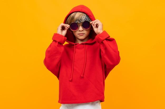 Stylowy młody chłopak w czerwonej bluzie i białej koszulce kładzie ręce na piersi