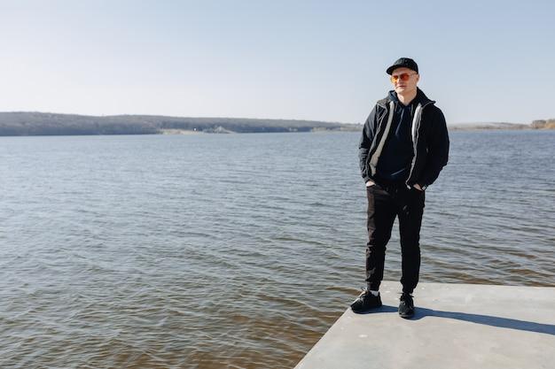 Stylowy młody chłopak w pomarańczowych okularach, kurtce i czapce, spaceruje po jeziorze wiosną lub jesienią