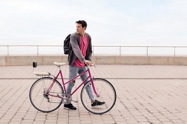 Stylowy młody człowiek chodzący z koncepcją ekologicznego transportu w stylu vintage