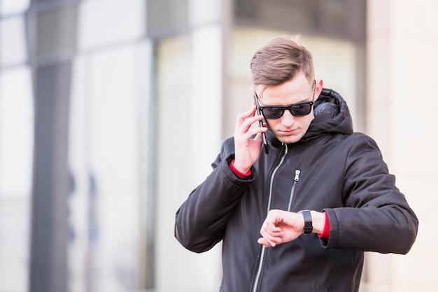 Stylowy młody człowiek rozmawia przez telefon komórkowy patrząc na czas na jego zegarek na rękę