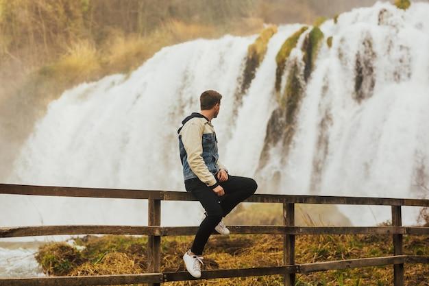 Stylowy młody człowiek siedzący w pobliżu niesamowitego wodospadu w terni we włoszech.