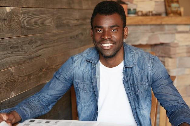 Stylowy młody człowiek siedzi w kawiarni