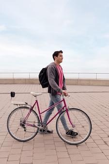 Stylowy młody człowiek spacerujący z zabytkowym rowerem