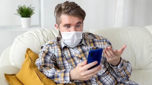 Stylowy młody człowiek trzyma telefon komórkowy z maską na twarz