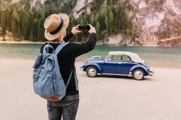Stylowy młody człowiek ubrany w modny kapelusz, zabawy na brzegu jeziora i robienie zdjęć krajobrazu, trzymając telefon komórkowy