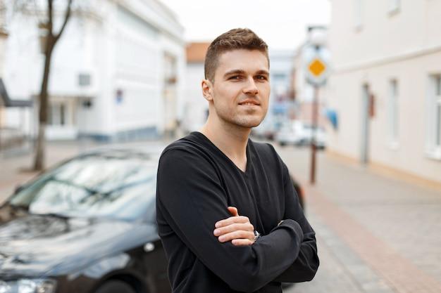 Stylowy młody człowiek w czarnej koszulce w pobliżu samochodu