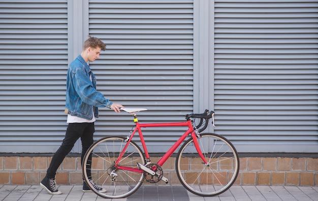 Stylowy młody człowiek w dżinsowej kurtce i rowerze na szarej powierzchni