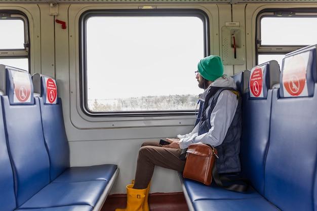 Stylowy młody człowiek w okularach siedzi w wagonie pociągowym z oznaczeniami dla pasażerów siedzących i wygląda przez okno. napis na siedzeniach: zachowaj dystans, usiądź tutaj.