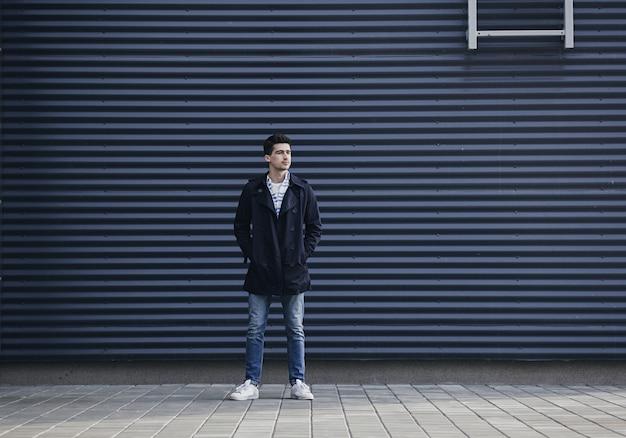 Stylowy młody człowiek w płaszczu i dżinsach stoi w pobliżu murów miejskich