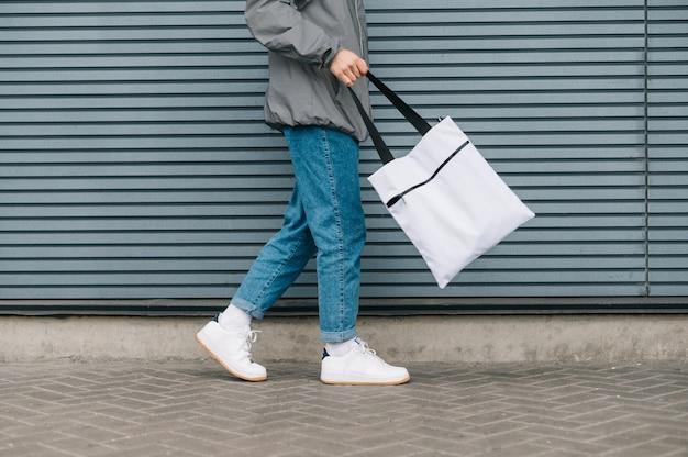 Stylowy młody człowiek w ulicznych ubraniach chodzenie z torby na zakupy wielokrotnego użytku na szary