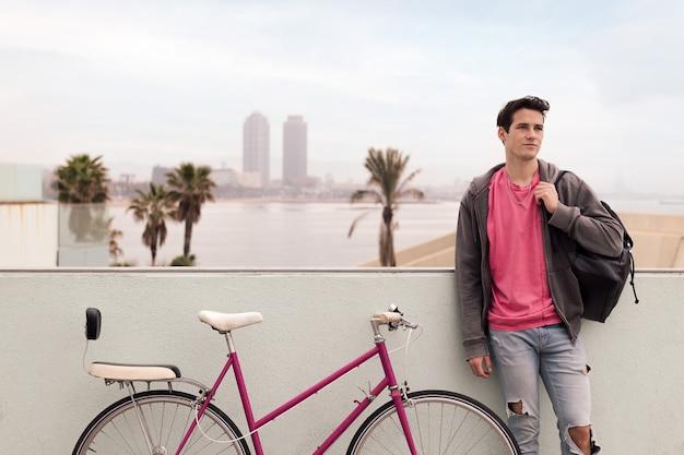 Stylowy młody człowiek z miasta przed miastem ze swoim zabytkowym rowerem