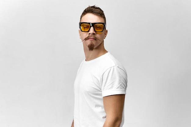 Stylowy młody człowiek z okulary i białą koszulkę ukrywa jedno oko