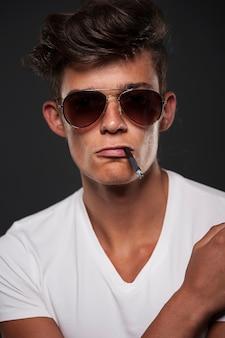 Stylowy młody człowiek z papierosem między ustami