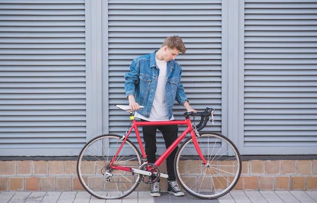 Stylowy młody człowiek z rowerem, w którym przebitego koła stoi na powierzchni ściany