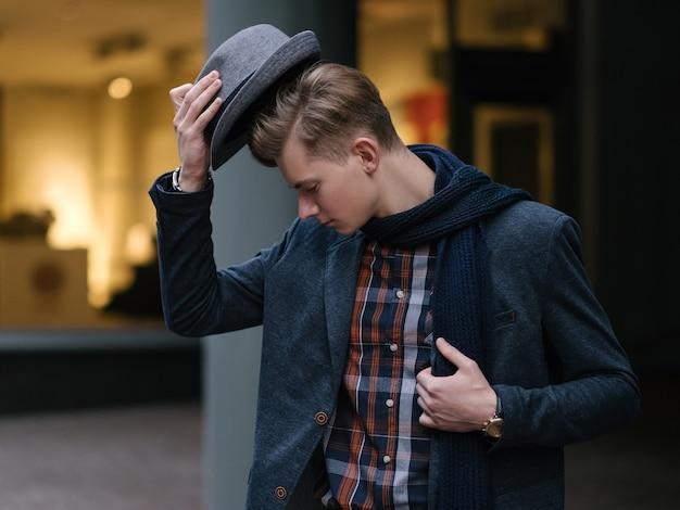 Stylowy młody człowiek zdejmujący kapelusz fashionistka i twórca trendów w stylu życia haute couture