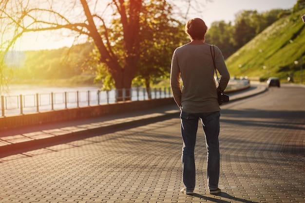 Stylowy młody fotograf spacerując po mieście z aparatem fotograficznym retro