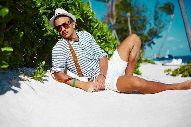 Stylowy młody mężczyzna modelu mężczyzna leżący na piaszczystej plaży w kapeluszu, hipster lato