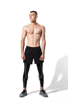 Stylowy, młody mężczyzna sportowiec praktykujący na tle białego studia, portret z cieniami. sportowo dopasowany model sprawdza się w ruchu i akcji. kulturystyka, zdrowy styl życia, koncepcja stylu.