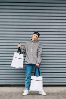 Stylowy młody mężczyzna stoi na szaro z ekologicznymi torbami w rękach i stylowymi ubraniami ulicznymi,