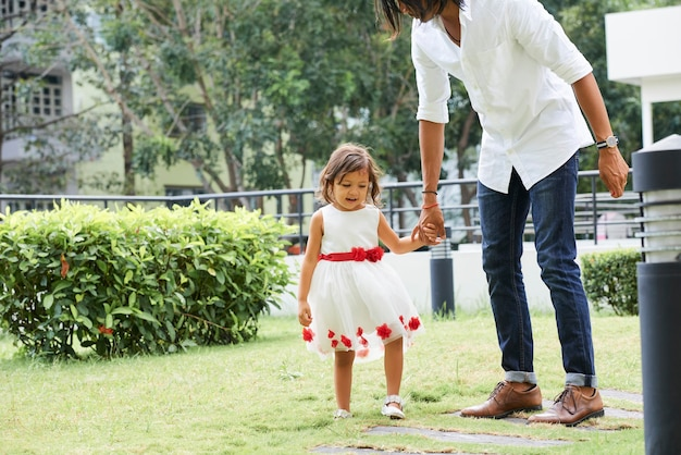 Stylowy młody mężczyzna trzymający rękę córki, gdy spacerują po podwórku w letni dzień