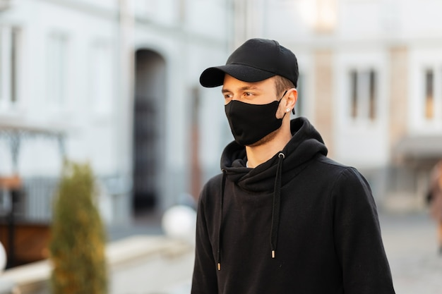Stylowy młody mężczyzna w czarnych ciuchach z czapką, bluzą z kapturem i maską ochronną covid spaceruje po mieście