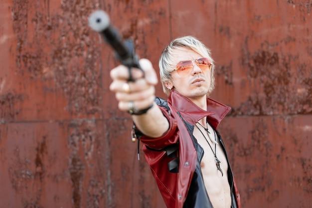 Stylowy młody mężczyzna z nagim torsem w modnej skórzanej kurtce w modnych czerwonych okularach strzela z broni vintage. facet blondyn na zewnątrz z pistoletem. styl retro.
