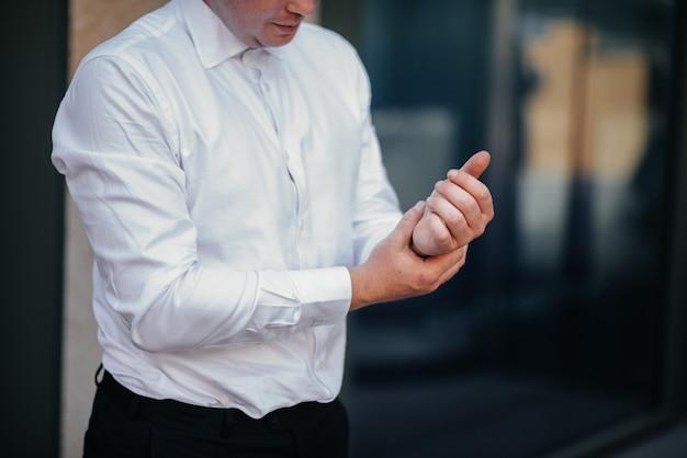 Stylowy młody mężczyzna zapinający mankiety na rękawach.