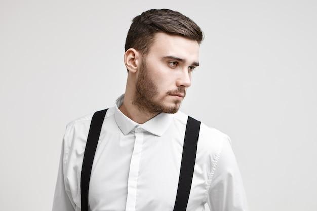 Stylowy, młody model mężczyzna z przystrzyżonym zarostem i fryzurą pozuje do ubrania lub reklamy fryzjera, patrzy z ukosa z zamyślonym, poważnym wyrazem twarzy. ludzie, uroda, styl i moda