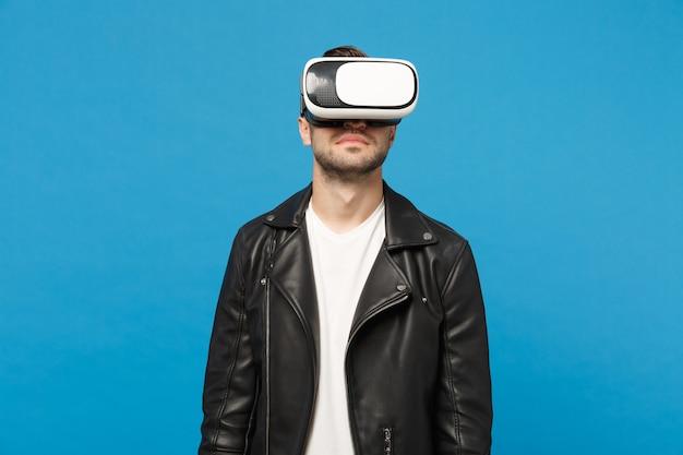 Stylowy młody nieogolony mężczyzna w czarnej kurtce biały t-shirt patrząc w zestaw słuchawkowy, rzeczywistość wirtualna vr na białym tle na tle niebieskiej ściany portret studio. koncepcja życia emocje ludzi. makieta miejsca na kopię.