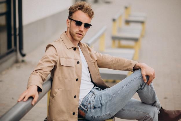 Stylowy młody przystojny mężczyzna siedzi na ławce