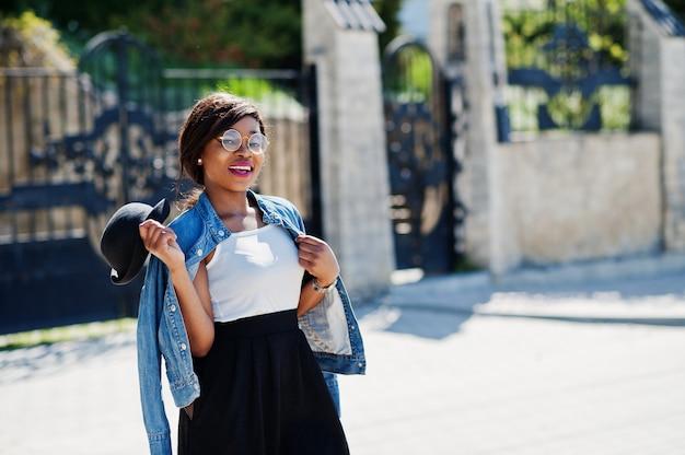 Stylowy model afroamerykanów w okularach kapelusz, dżinsową kurtkę i czarną spódnicę pozował na zewnątrz.