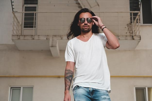 Stylowy model brodaty mężczyzna pozowanie z okulary przeciwsłoneczne