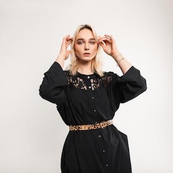 Stylowy model młoda kobieta w modne ubrania prostuje fryzurę w pokoju. europejska urodziwa blondynka z seksownymi ustami w czarnej eleganckiej sukience z paskiem lampart pozowanie w pobliżu ściany w pomieszczeniu.