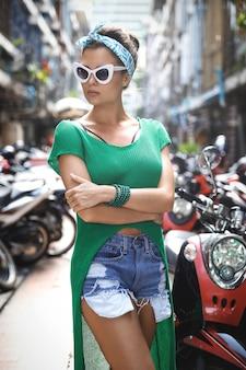 Stylowy model w zielonej koszuli i chustce pozuje na parkingu z dużą ilością skuterów