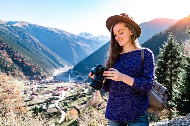 Stylowy modny hipster kobieta podróżnik fotograf z aparatem w filcowym kapeluszu podczas robienia zdjęć gór i jeziora uzungol w trabzon podczas podróży po turcji