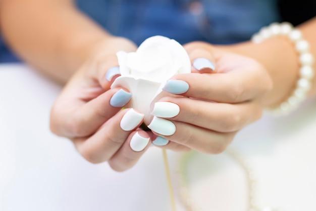 Stylowy modny kobiecy manicure. piękne dłonie młodej kobiety na tle kwiatów i koralików z pereł