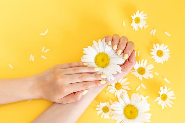 Stylowy modny manicure żeński. piękne młode kobiety ręce na żółtym tle.