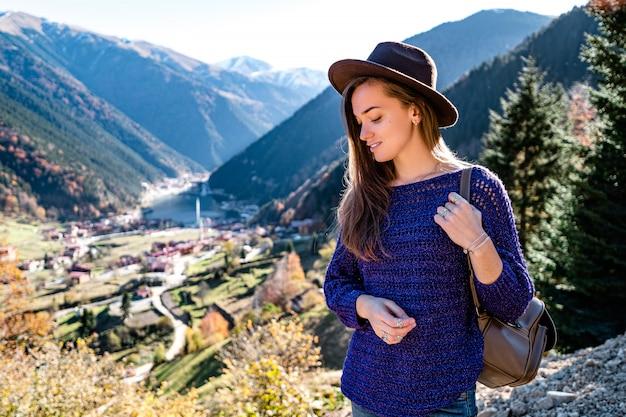 Stylowy modny szczęśliwy hipster kobieta podróżnik w brązowy kapelusz z plecakiem w górach i jeziorem uzungol w trabzon podczas podróży po turcji