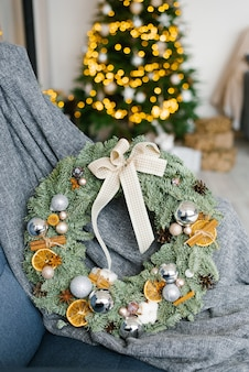 Stylowy, modny wieniec świąteczny z bombkami, suszonymi plasterkami pomarańczy i cynamonem w wystroju pokoju