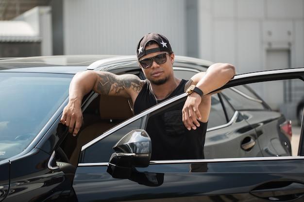 Stylowy murzyn stojący obok swojego fantazyjnego samochodu