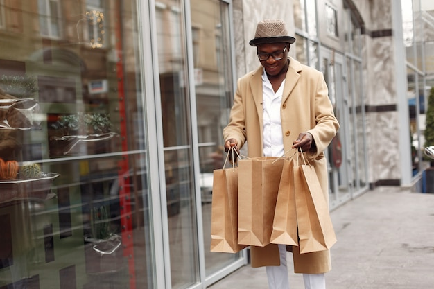 Stylowy murzyn w mieście z torby na zakupy