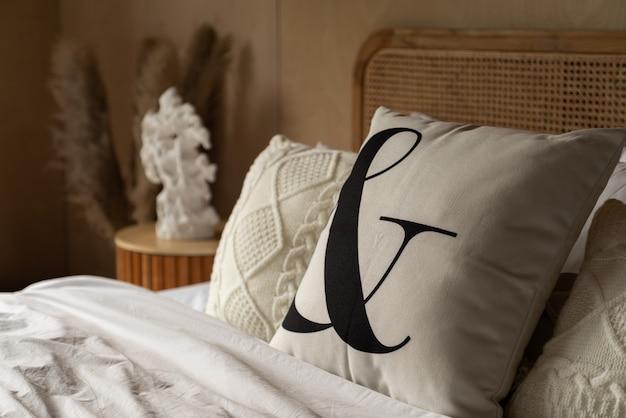 Stylowy narożnik do sypialni z rattanowym zagłówkiem i dekoracją miękkiej poduszki