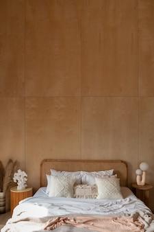 Stylowy narożnik do sypialni z rattanowym zagłówkiem i łóżkiem z miękkimi białymi poduszkami ze ścianą ze sklejki