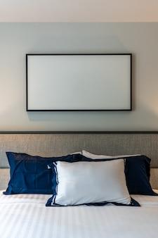 Stylowy narożnik do sypialni z zagłówkiem z szarej tkaniny i łóżkiem z miękkimi poduszkami z granatowo-białą pomalowaną ścianą w tle / przytulny wystrój wnętrza / nowoczesne wnętrze