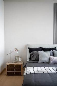 Stylowy narożnik do sypialni ze skórzanym zagłówkiem i łóżkiem z miękkimi poduszkami z pomalowaną na biało ścianą w tle / przytulny wystrój wnętrza / nowoczesne wnętrze