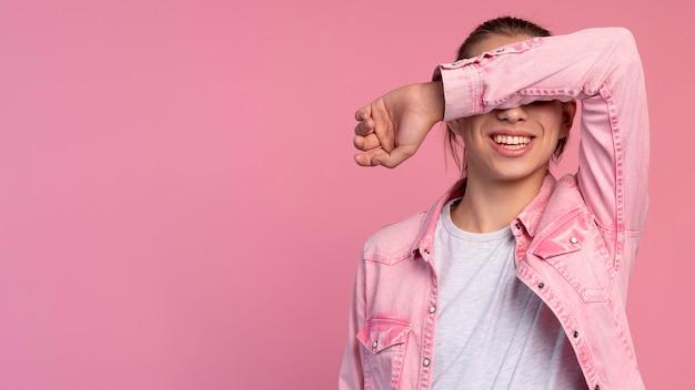 Stylowy nastoletni chłopak w różowym pozowanie z kopią przestrzeni