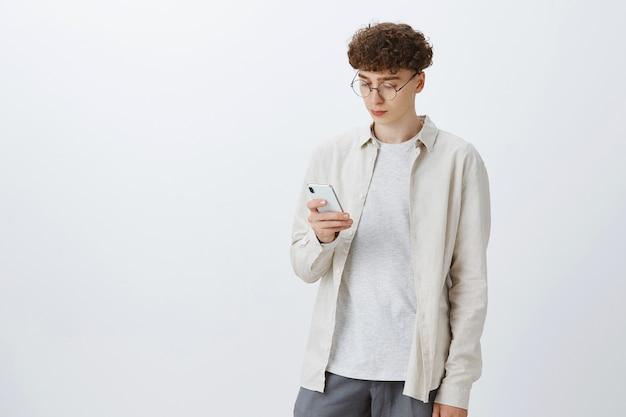 Stylowy nastoletni facet pozuje na białej ścianie